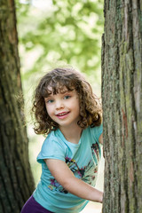 Close up summer portrait of a cute pretty smiling preschool girl with tangled hair, standing between two trees.