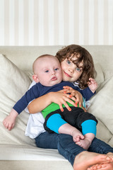 Cute portrait of sister and brother siblings holding each other on a couch. Small girl and a baby boy.