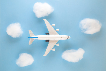 High angle view of airplane toy and clouds on blue sky background