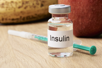 Diabetes - Eine Ampulle mit Insulin steht auf einem Tisch und daneben liegt eine Spritze. Im Hintergrund sind eine Apfel und eine Banane zu sehen