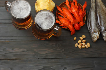 Glass beer with crawfish, dried fish and wheat ears on dark wooden background. Beer brewery concept. Beer background. top view with copy space