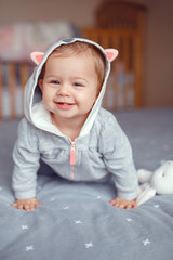 Portrait of cute adorable Caucasian blonde smiling baby girl in grey pajama with fox cat animal hood in bedroom. Natural emotion face expression. Happy childhood lifestyle concept