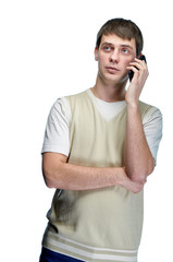 A young man in stylish casual clothes chatting on the phone with his lover. Pensive, cute, dreamy, romantic guy with a smartphone isolated. The boy is talking on the mobile.