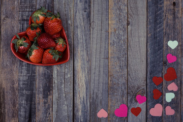 Heart shaped bowl of strawberries on wooden background