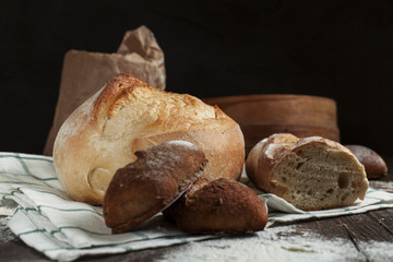freshly baked bread on a wooden table on a dark background