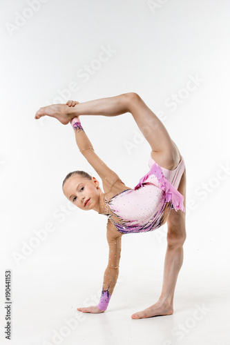 b719ccbbc9e8 A young teenage girl in leotard shows gymnastic and ballet exercises on a  white background.