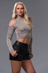 Beautiful Blonde Woman in a Gray Copy Top and Black Shorts Isolated on a Gray Background