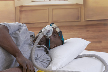 Healthcare concept,African, American Man with obstructive sleep apnea sleeping well with cpap machine ,Man laying in bed wearing cpap mask, on white backgroud