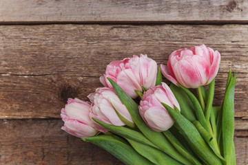 Bouquet of pink tulips over shabby wooden table. Spring greeting card happy mother day copy space