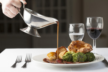 Traditional British roast dinner of rare beef, yorkshire pudding, roast potatoes and brocolli with gravy being poured over from a gravy boat.