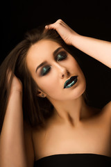Glamorous brunette lady with art metallic green makeup posing with closed eyes. Closeup portrait at studio on a dark background