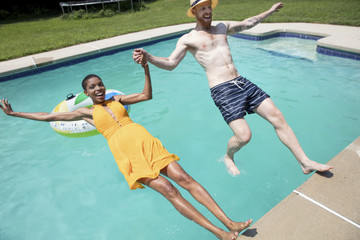 High angle view of happy couple jumping into swimming pool at tourist resort