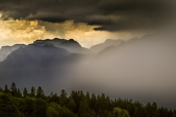 Scenic view of storm clouds over mountains during sunset