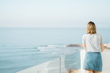 Woman looking at view while standing against sea and sky in balcony