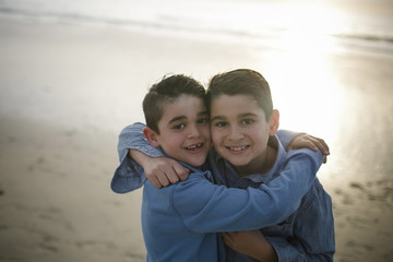 Portrait of happy brothers standing at beach during sunset