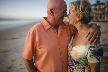 Smiling senior couple looking at each other while standing by sea against sky