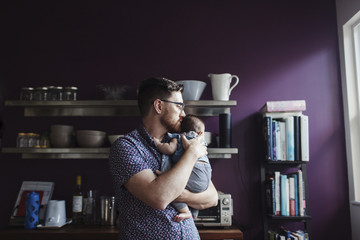 Father carrying daughter while standing in kitchen at home