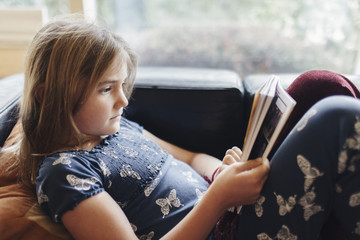 Girl reading book while lying on sofa at home