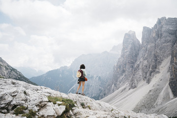 Back view of female hiker standing on the mountain against cloudy sky