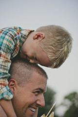 Side view of happy father carrying son on shoulders while standing against sky