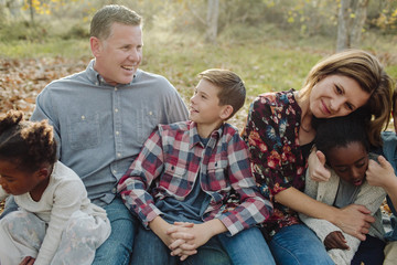 Happy family sitting on field at park