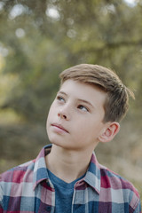 Close-up of thoughtful boy looking away while standing at park
