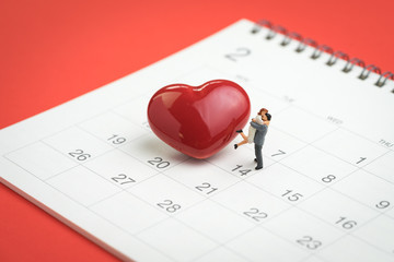 Valentine day concept miniature figures sweet couple standing with shiny red heart shape on 14th February calendar on red background