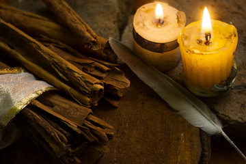 Cinnamon sticks on wood table with candles and feather
