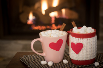 Romantic Valentine's Day, Warm Fireplace Scene with Red and Pink Cocoa Mugs with red Hearts in Cozy Living room with space for copy, text, or your words or Design.  Horizontal natural lighting