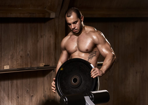Athlete man with weightlifting plate