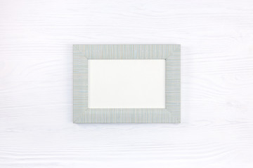 empty gray wood photo frame on white wooden surface