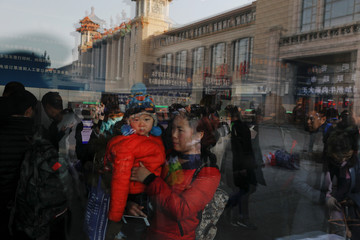 Passengers are reflected in the widow of a ticket booth at the Beijing Railway Station as the annual Spring Festival travel rush begins ahead of the Chinese Lunar New Year, in central Beijing