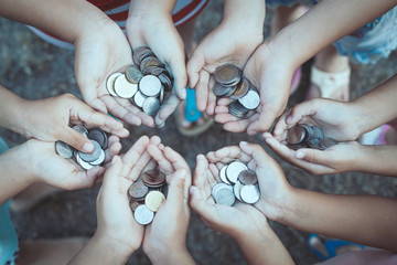 Group of children holding money in hands in the circle together as finance and charity concept