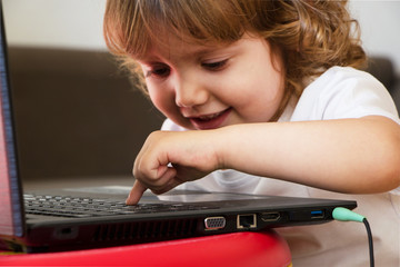 little child with headphones playing computer