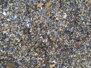 Polished glass pieces in the rocks at Glass Beach near Fort Bragg, California. Top down view.