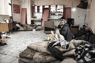 Poor homeless men sitting in abandoned house