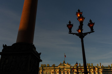 Palace square. Facade of the Winter Palace, house of the Hermitage Museum, Alexander Column and working flashlight in St. Petersburg, Russia.