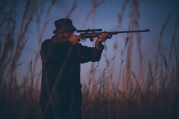 Hunter aiming prey on field with his rifle