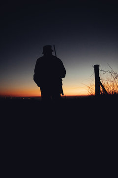 Silhouette of hunter with gun at sunrise