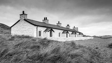 A black and wjite photograph of a row of old fishermans cottages on the beach
