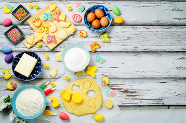 Wood background with Sugar Easter cookies and ingredients for baking