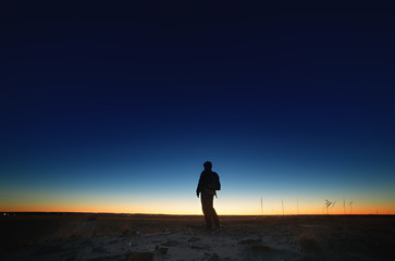 A tourist on the road against the background of a bright sunset and a cloudless sky.