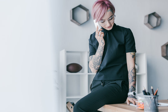 smiling young businesswoman with tattoos talking by smartphone at workplace