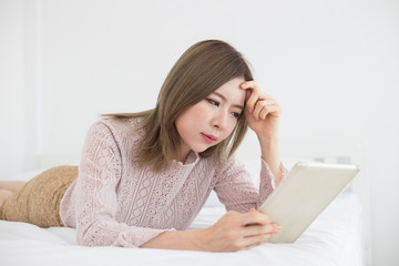 Asian woman looking in tablet on bed