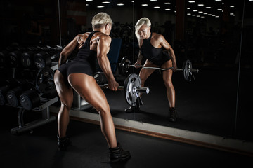 Sexy sporty girl. Strong girl on training hall with dumbbells.