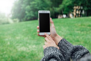Młoda kobieta robi zdjęcie telefonem w parku. Wall mural