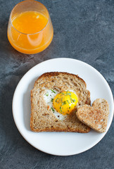 Breakfast Valentine's Day. On the plate is toast with fried eggs inside a heart and orange juice.