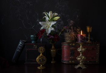 Dark still life with flowers and antique items