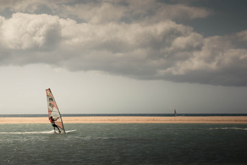 Windsurf in beautiful pastel tones scenery with cloudy sky and shimmering water. Playa de Sotavento, Fuerteventura Canary islands, Spain.