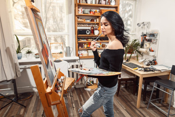 Smiling girl paints on canvas with oil colors in workshop